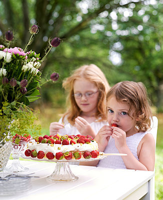 Two children in garden eating strawberry cake - p972m1088568 by Patric Johansson