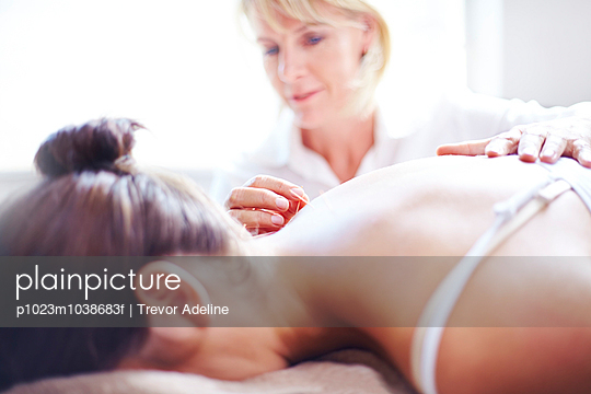 Acupuncturist applying acupuncture needle to womanÕs neck