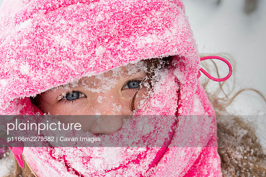 A portrait of a girl Dressed for Winter covered in snow - p1166m2279582 by Cavan Images