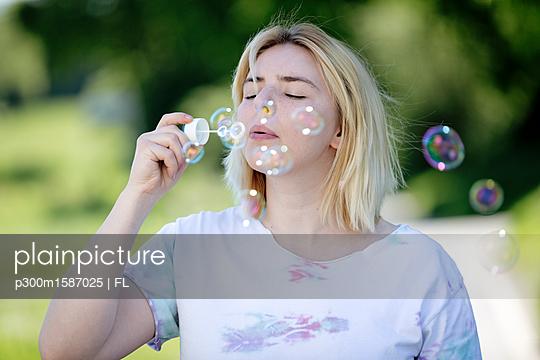 Young blonde woman blowing soap bubbles outdoors - p300m1587025 von FL photography