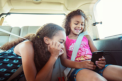 Girls looking at smart phone while traveling in car - p1166m1225970 by Cavan Images