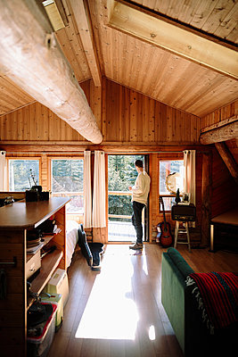 Serene man drinking coffee at sunny cabin doorway - p1192m2094215 by Hero Images