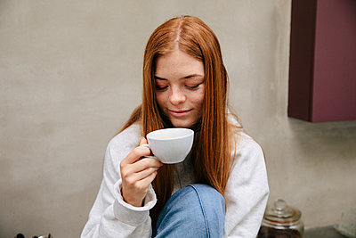 Teenage girl with red hair has a cup of coffee - p1640m2242095 by Holly & John
