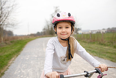 Smiling girl on bicycle wearing cycling helmet - p300m2256077 by Katharina Mikhrin