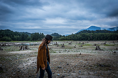 Young Adult Man Walking Across Dried Up Lake with Wildfire Smoke in Background - p694m1069875 by Charlie Miller