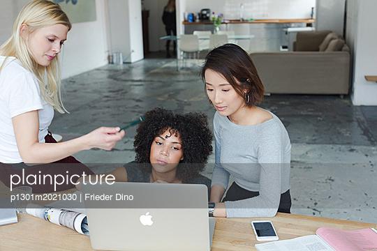 Brainstorming am Computer von drei jungen, modernen Kolleginnen  - p1301m2021030 von Delia Baum