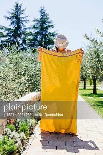 Girl behind yellow bath towel - p1621m2291763 by Anke Doerschlen