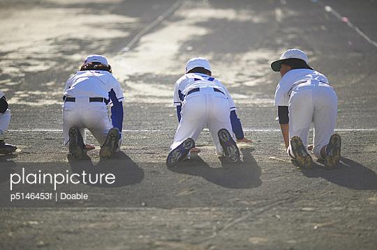 Boys in baseball uniform crawling