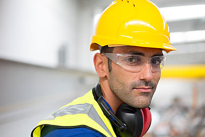 Portrait serious male worker in protective eyewear and hard-hat in factory - p1023m2187485 by Sam Edwards