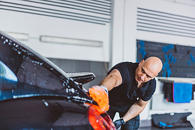 Worker washing car with sponge while standing in workshop - p1166m2060370 by Cavan Images