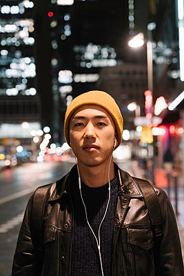 Portrait of stylish man with yellow hat and earphones in the city at night - p300m2188120 by Hernandez and Sorokina