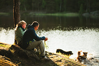 Couple sitting at lake - p312m2079939 by Matilda Holmqvist