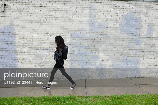 Woman with backpack walking on wet urban sidewalk - p1192m2123441 by Hero Images