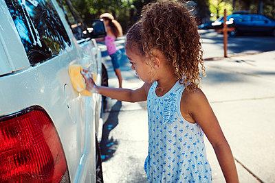 Girls washing car in driveway - p1166m1225975 by Cavan Images