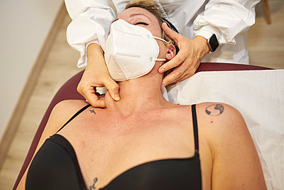 Medical physiotherapist gives a neck massage to his patient. - p1166m2234849 by Cavan Images