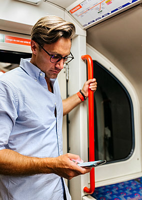 UK, London, businessman in underground train looking at cell phone - p300m2062073 von Marco Govel
