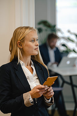 Young businesswoman with cell phone in office - p300m2160140 by Gustafsson