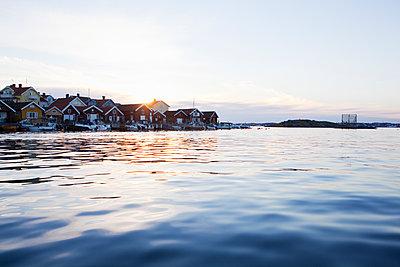 Sweden, Bohuslan, Skafto, Houses and motorboats by sea at sunset - p352m1126304f by Carina Gran