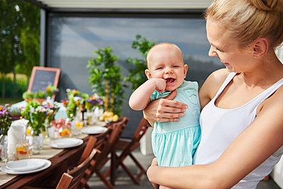 Young woman carrying baby daughter at family lunch by patio table - p429m1494222 by Gpointstudio
