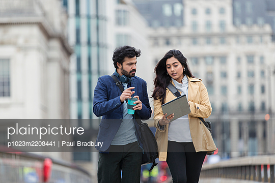 Business people with digital tablet and coffee on city bridge - p1023m2208441 by Paul Bradbury