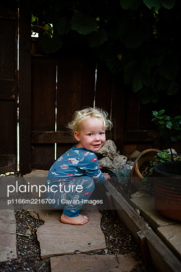 Two Year Old Smiling for Camera Crouching in Front Yard - p1166m2216709 by Cavan Images