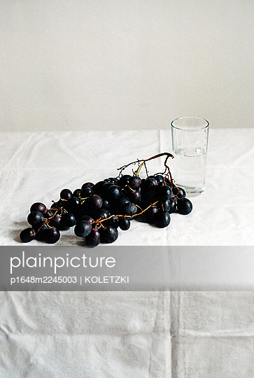 Black grapes and water glass on tablecloth - p1648m2245003 by KOLETZKI