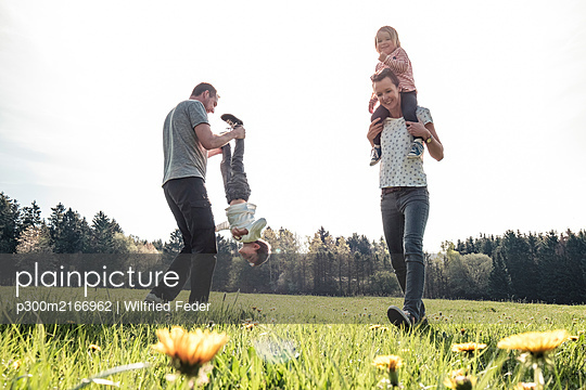 Happy family with two kids having fun on a meadow in spring - p300m2166962 by Wilfried Feder