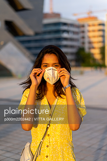 Young woman wearing face mask while standing in city - p300m2202442 by VITTA GALLERY