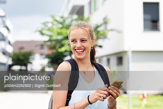 Smiling young woman using phone - p924m2292502 by Sigrid Gombert