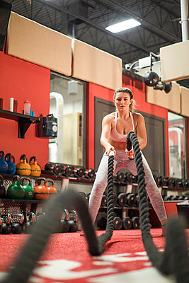 Fit intense woman doing battle rope exercise in the gym - p1166m2084312 by Cavan Images
