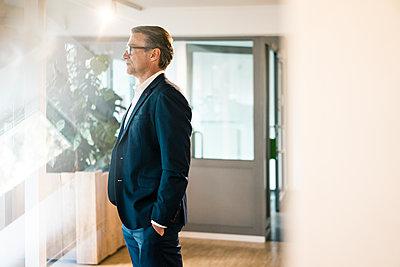 Serious mature businessman standing in office thinking - p300m2005583 von Joseffson
