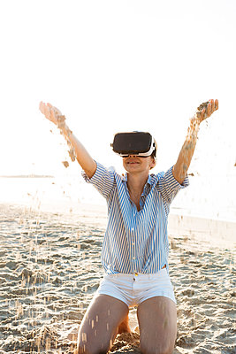 Thailand, woman using virtual reality glasses on the beach in the morning light - p300m2080186 by Epiximages