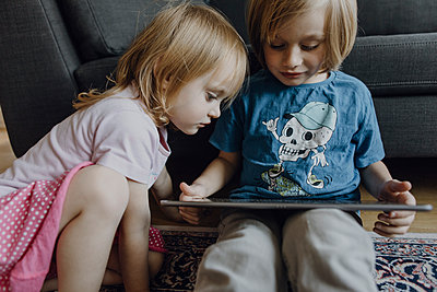 Brother and little sister sitting on the floor at home using digital tablet - p300m2080462 by Johanna Lohr