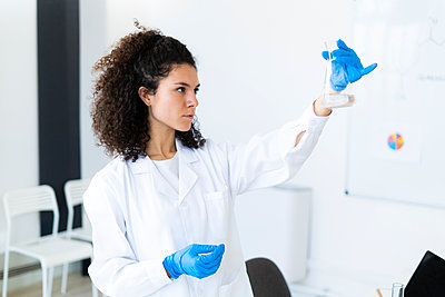 Confident female scientist examining chemical solution in hospital - p300m2251588 by Giorgio Fochesato