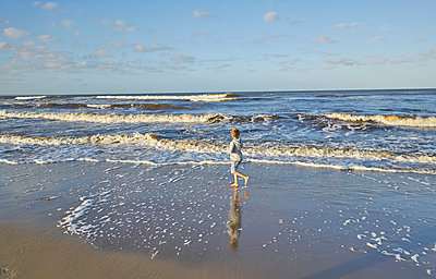 Boy in beach playing in lapping waves, Polonio, Rocha, Uruguay, South America - p429m1519599 by Stephen Lux