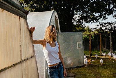 Junge Frau steht gedankenversunken auf Hühnerhof - p432m2293162 von mia takahara