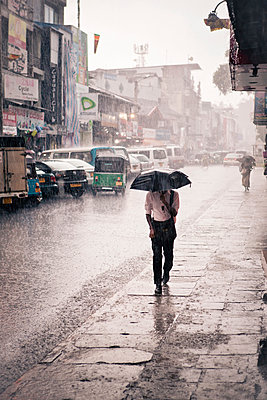 Man walking in the rain - p795m1031487 by Janklein