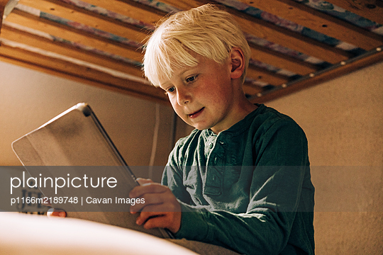 Young boy working on technology - p1166m2189748 by Cavan Images