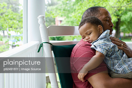 A grandfather holding his sleeping grandson - p9249181f by Image Source