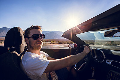 Young man driving convertible on a country road, Sierra Nevada, USA - p1084m857925 by Operation XZ