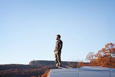 Man with hands in pocket standing on camper van against clear sky - p1166m1231453 by Cavan Images