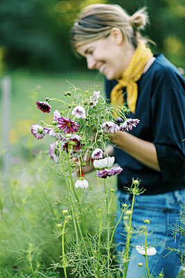 Millennial woman working at her flower farm making bouquets - p1166m2207824 by Cavan Images