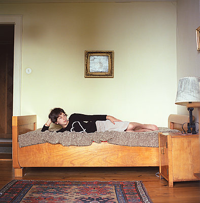 A child lying on a bed  - p1610m2185282 by myriam tirler