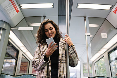 Smiling young woman using smartphone on a subway - p300m2143397 by Hernandez and Sorokina