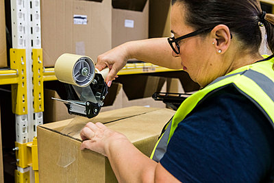 Female worker packing cardboard box with adhesive tape at distribution warehouse - p426m2018878 by Maskot
