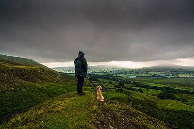 A man stands with his dog on a grassy hill looking out over the lush, green landscape under a stormy sky; North Yorkshire, England - p442m1449008 by John Short