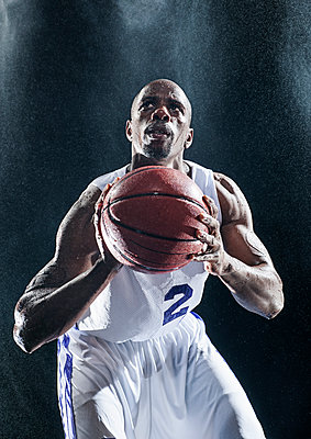 African American basketball player standing in rain - p555m1454258 by Erik Isakson