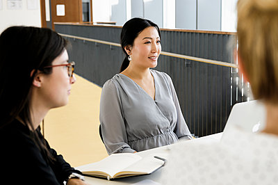 Germany, Bavaria, Munich, Women talking at desk during meeting - p924m2271302 by suedhang photography