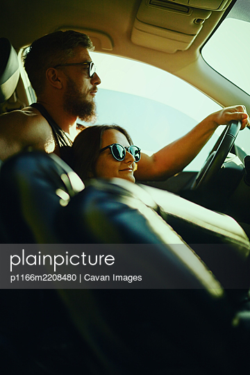 A woman and a man travel in a car in the summer. - p1166m2208480 by Cavan Images
