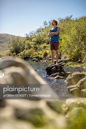 Junger Mann mit verschränkten Amen am Flussufer - p1355m1574227 von Tomasrodriguez